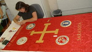 Skilled embroideress working on clerical banner